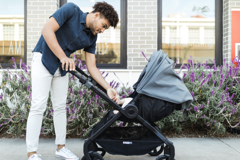 A baby faces dad in a stroller