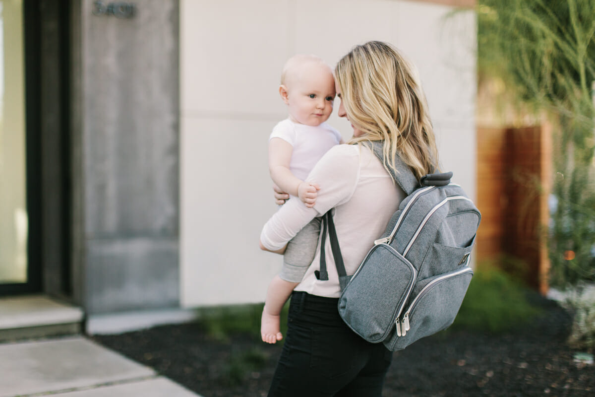 woman holding her baby and diaper bag