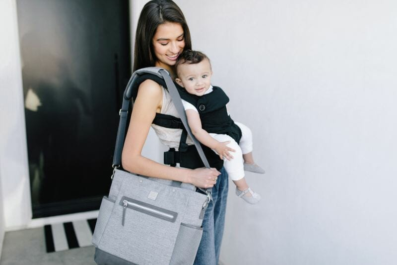 woman holding diaper bag and baby