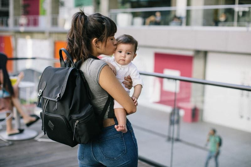 mom holding baby with backback diaper bag on