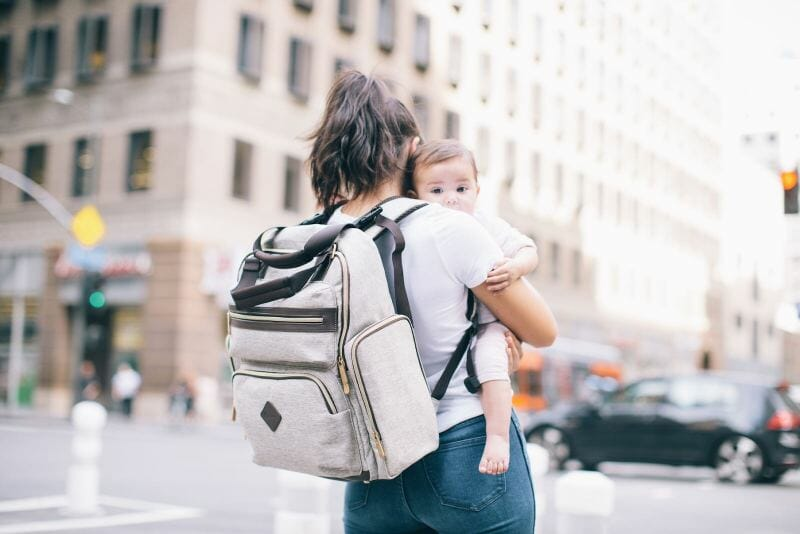 mom holding baby in city with backpack diaper bag on her back