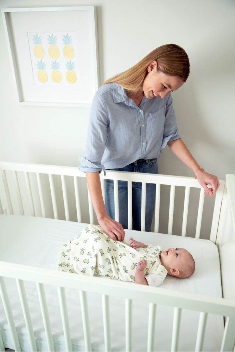 mom looking at sleeping baby in crib in ergobaby swaddler